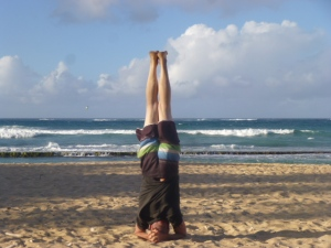 Beach yoga, headstands on the shoreline